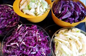 Red and green cabbage, sliced and salted.