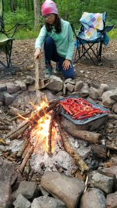 girl cooking over fire